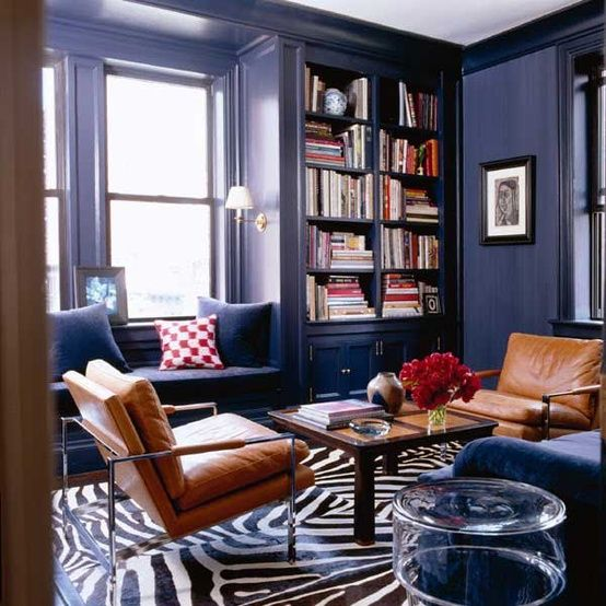 via  minnickinteriors.com  / The inky blue walls look amazing with the brown, leather chairs and zebra rug.