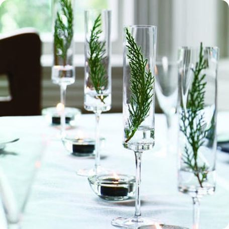 via centsationalgirl.com - sprigs of evergreen in champagne flutes.  simple elegance.