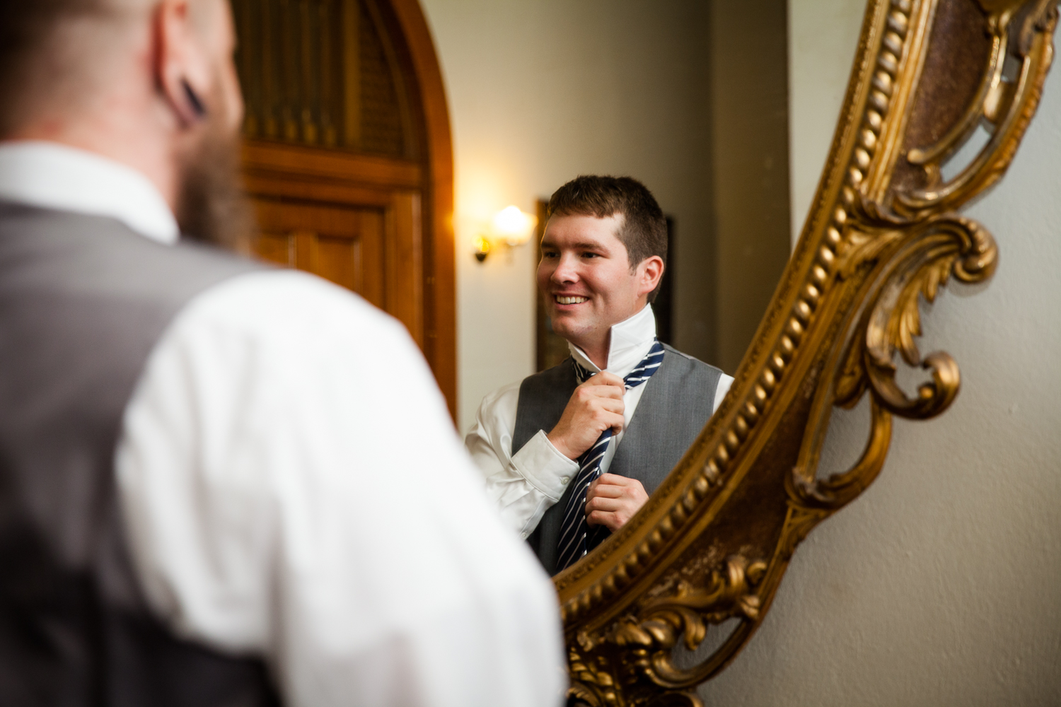 A Syracuse groom adjusts his tie in the mirror