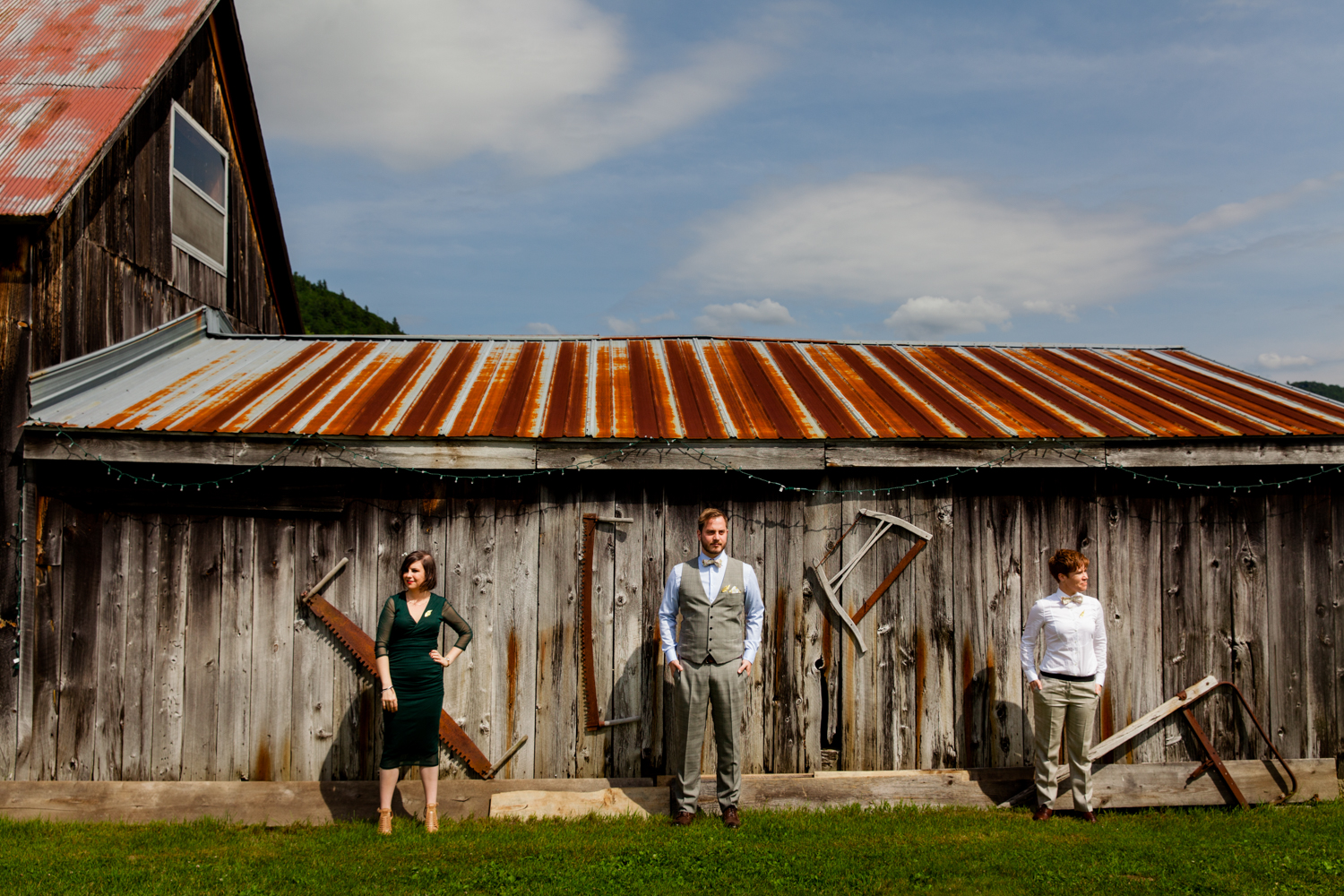 A groom and his grooms women stand in front of a barn in upstate, NY.