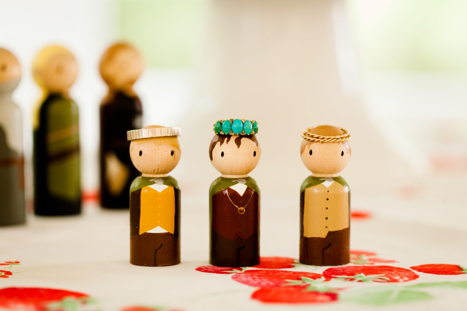 A close up of wedding rings on homemade hobbit figurines