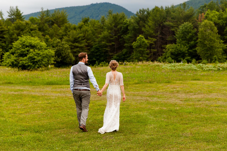 Bride and groom walk into a field
