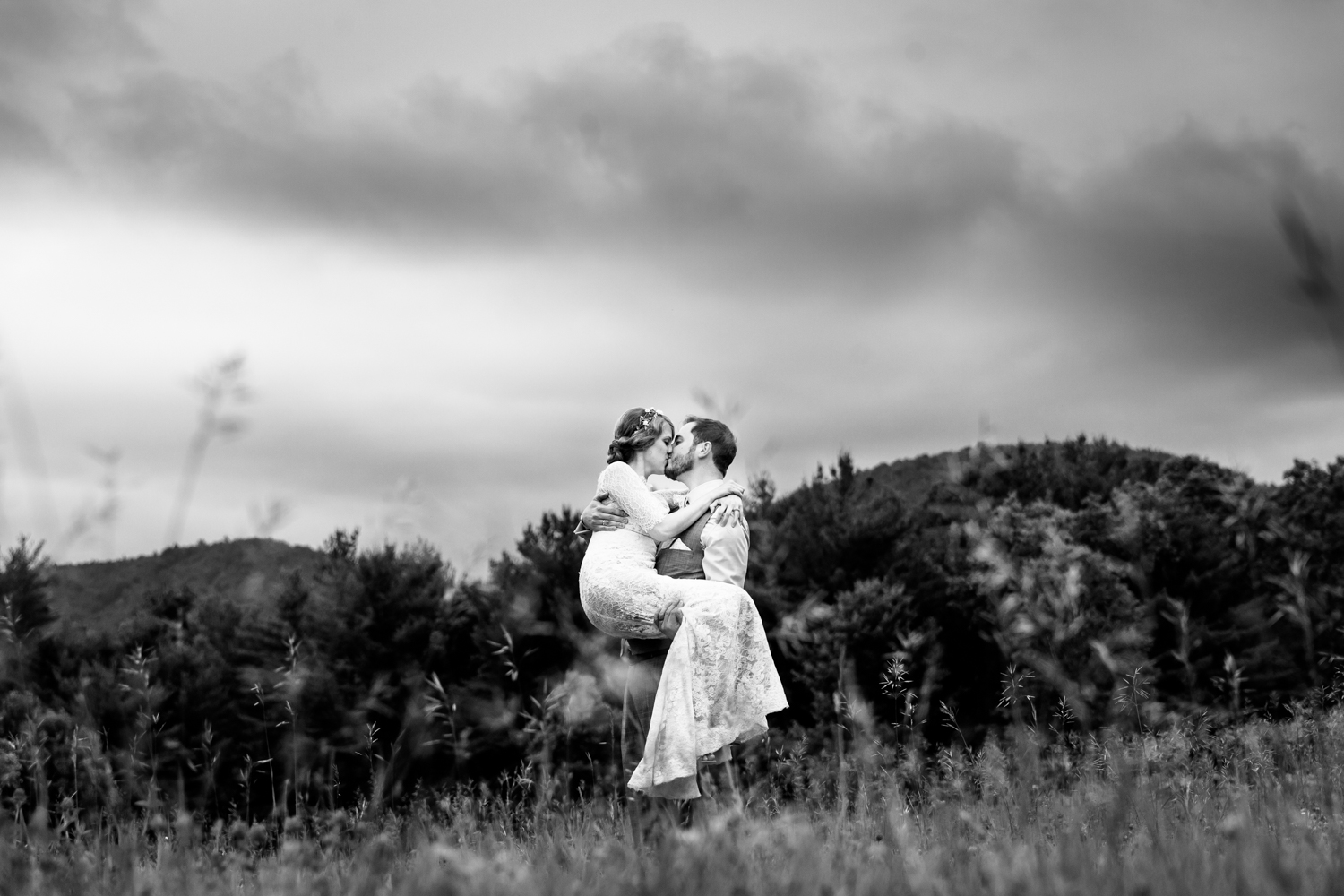 A groom carries a bride in a field
