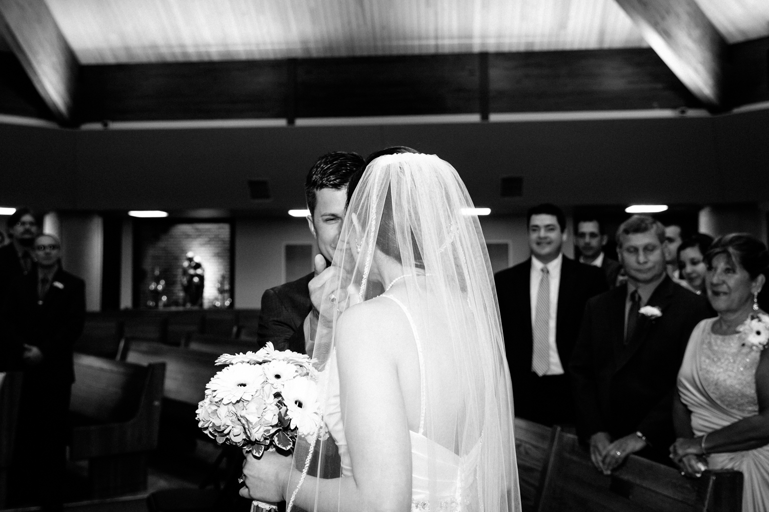 A touching bride and groom moment at Holy Family Church in Syracuse, NY.