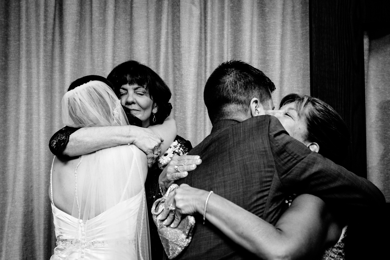 The bride and groom hug their mothers after the ceremony