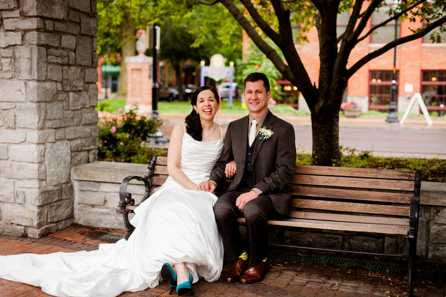 Bride and groom sit on bench laughing