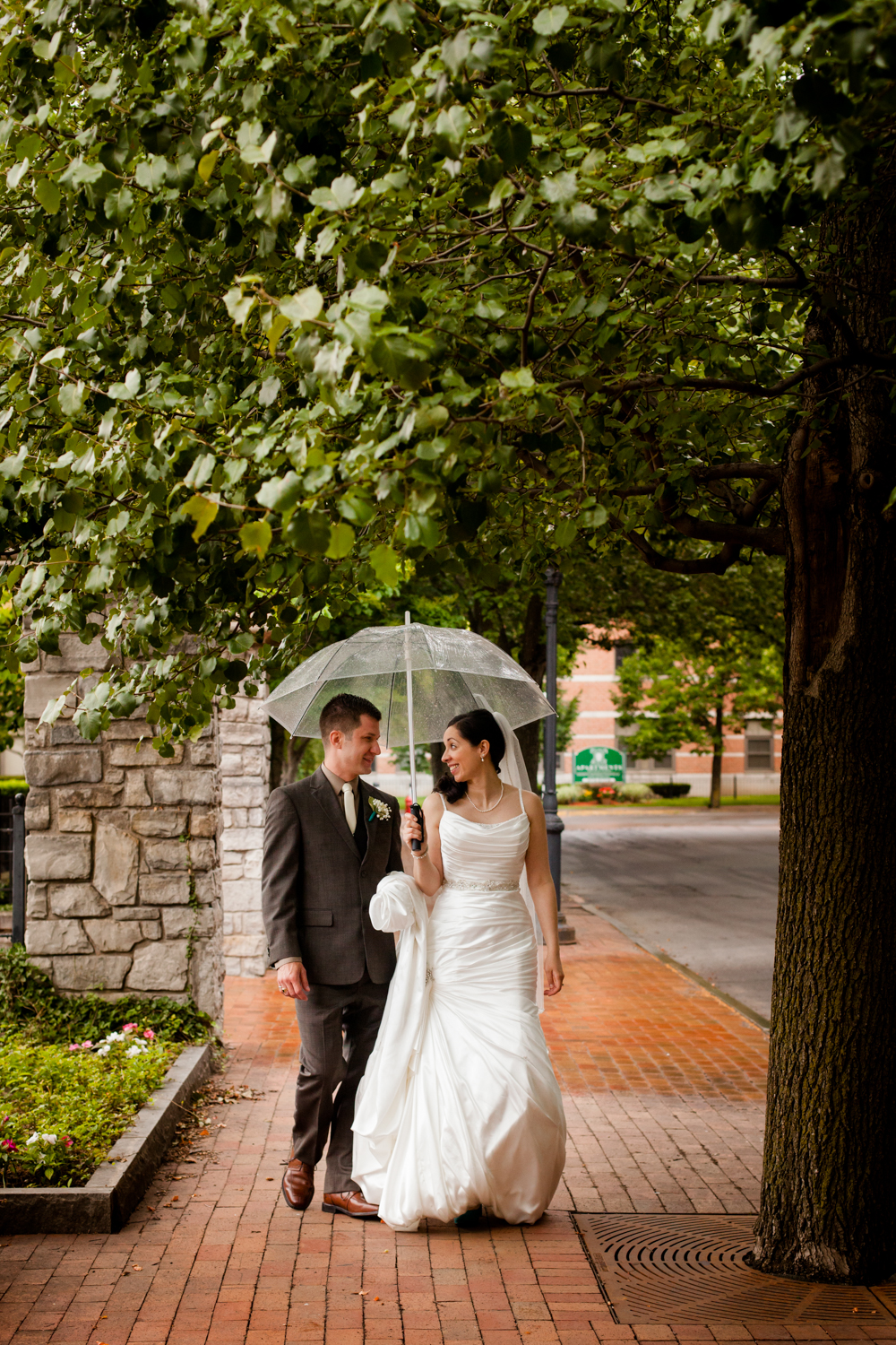 Bride and groom share a moment under an umbrella