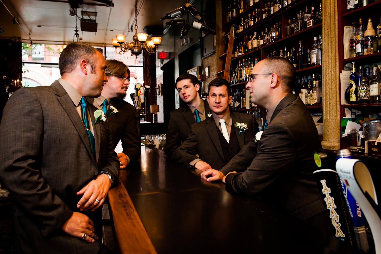 Groomsmenstand around a bar