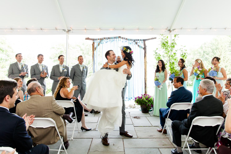 Groom carries bride down aisle