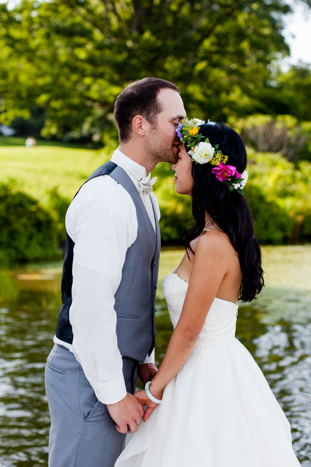 bride and groom kiss on a dock