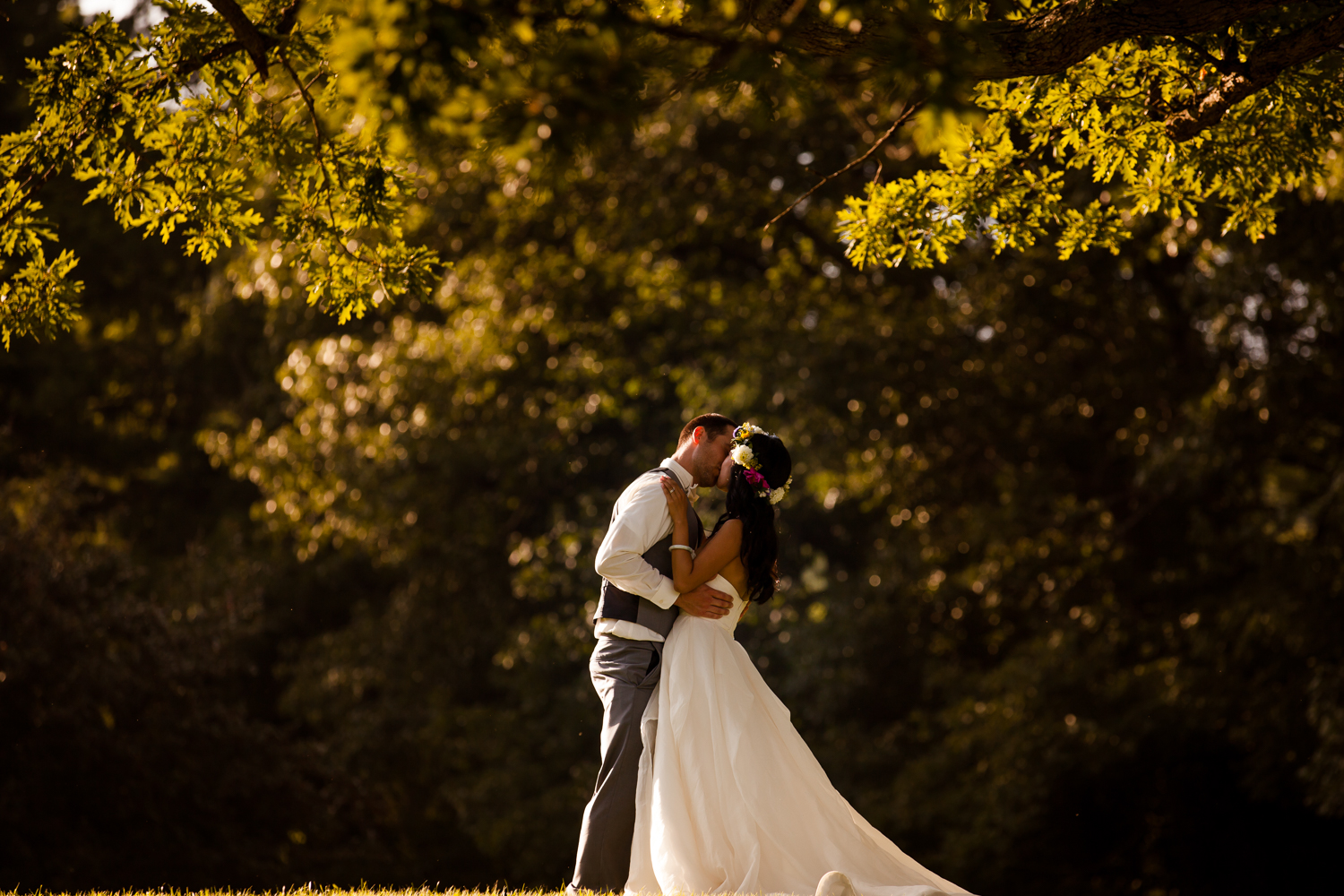 Beautiful bride and groom during dusk kissing