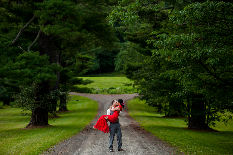 Groom holds bride on road