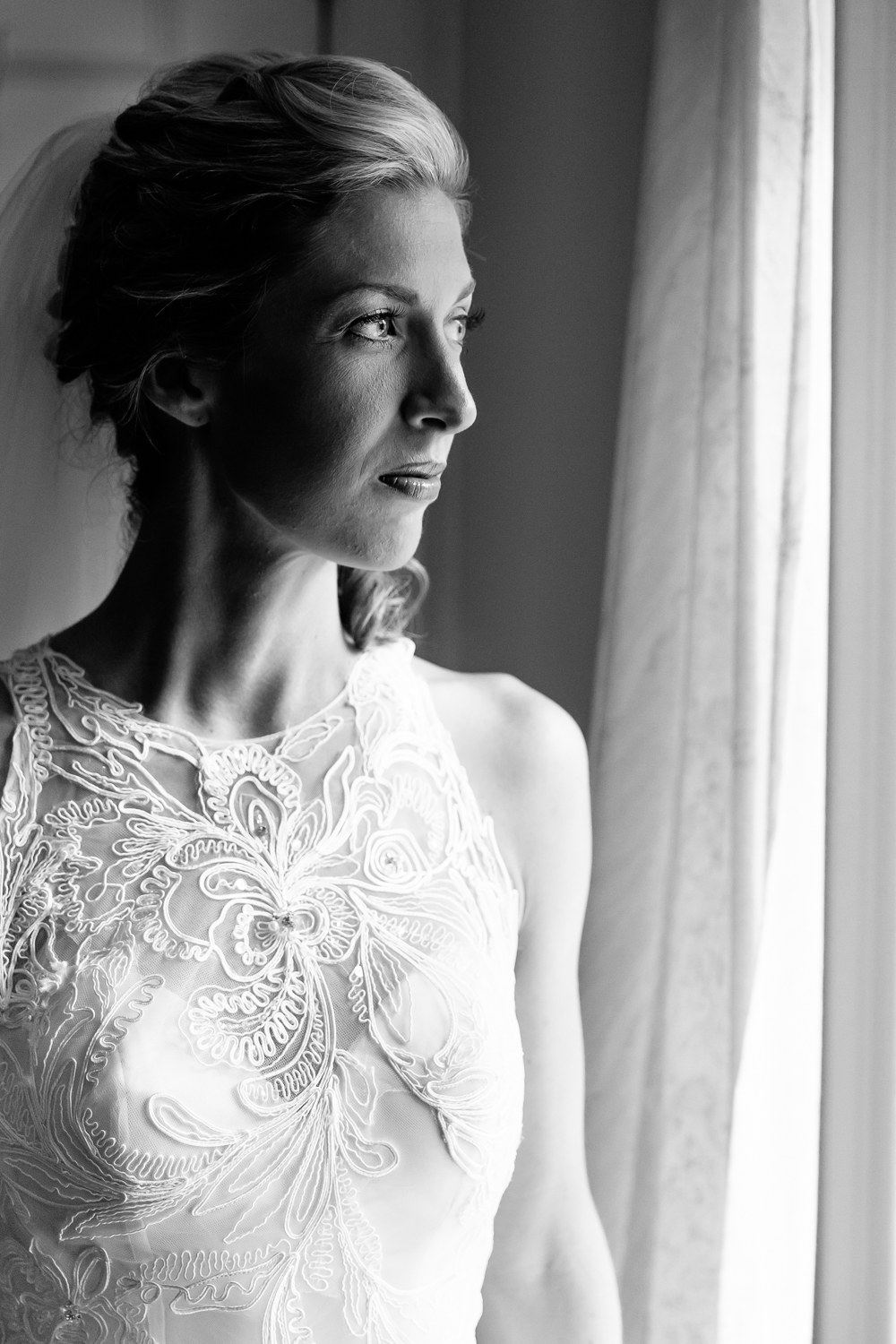 A bride looks out the window before her wedding.