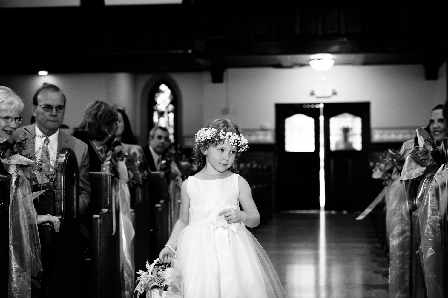 The flower girl walks down the aisle.