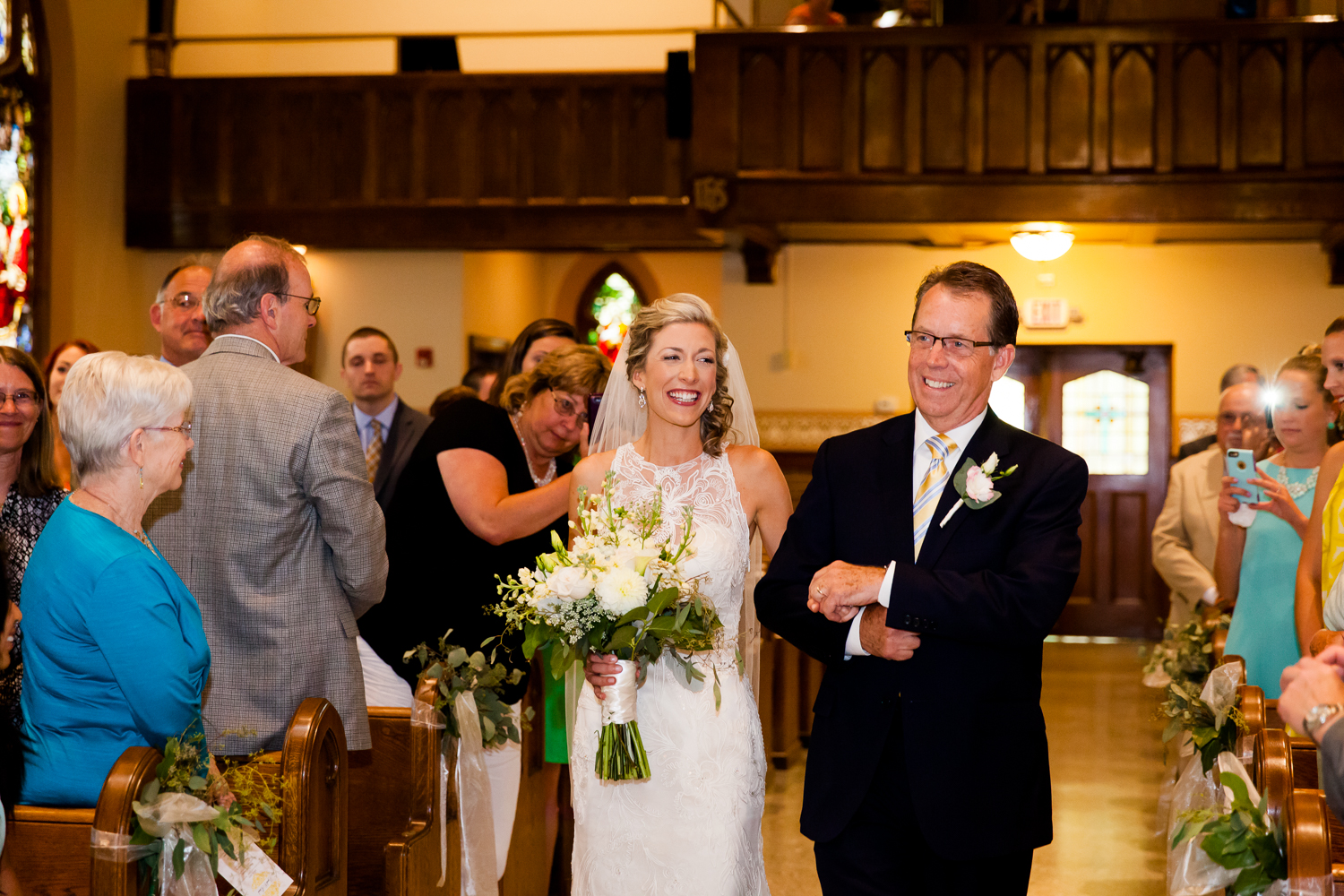 The bride walks down the aisle with her father on her wedding day.