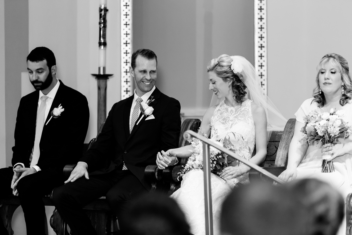 The bride and groom hold hands during their church ceremony.