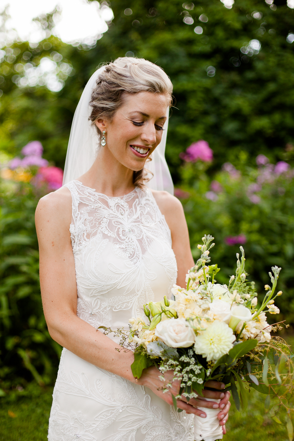 A bride gazes down at her flowers.