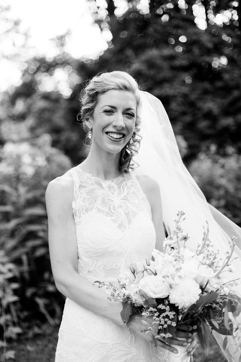 the bride smiles wide in a black and white photograph.
