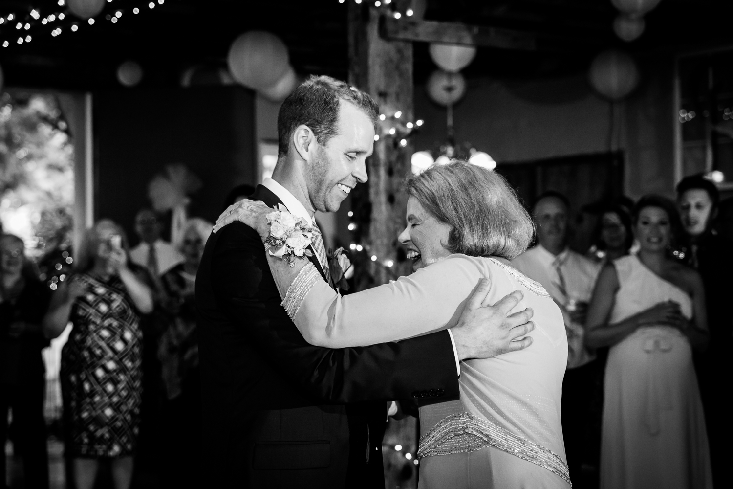 Mother and groom share a dance in a barn.