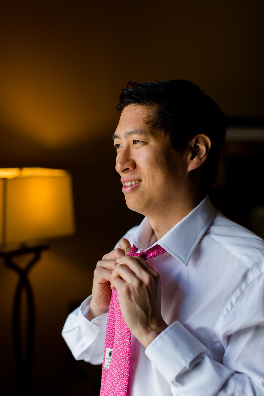 Groom adjusts his tie.