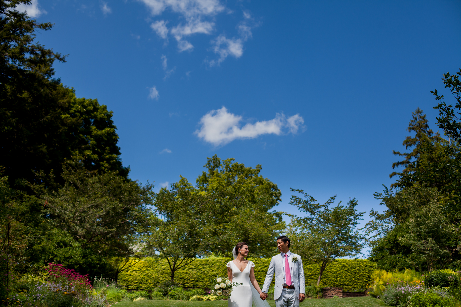 Bride and groom pose in a garden.