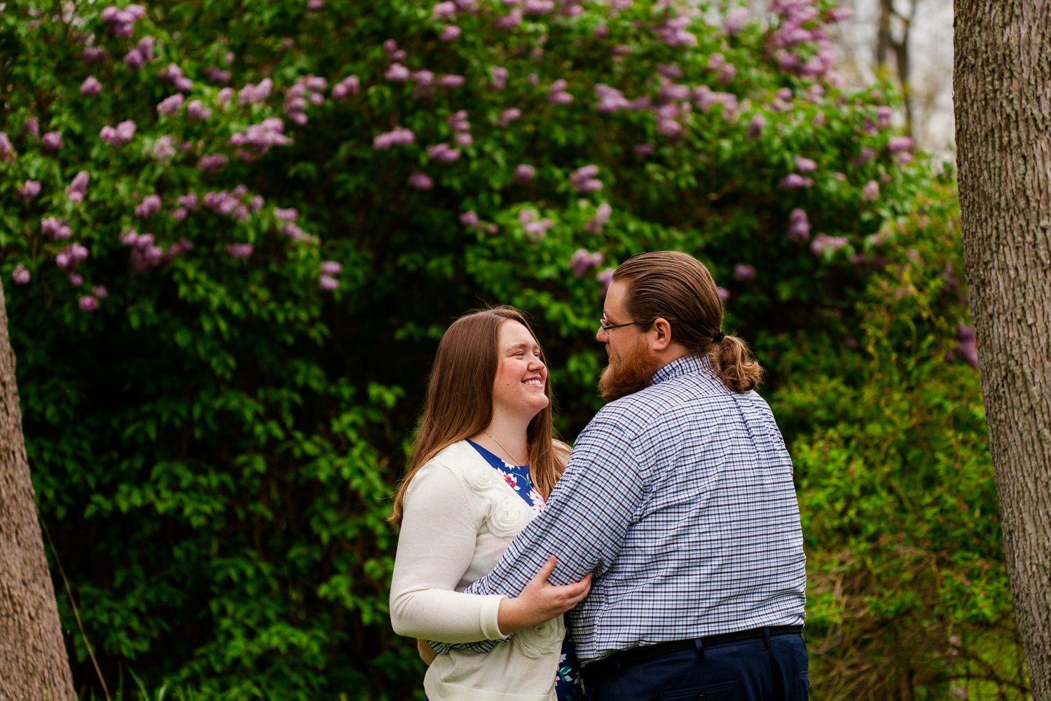 Woman smiles at man in front of lilac bush during engagement shoot.