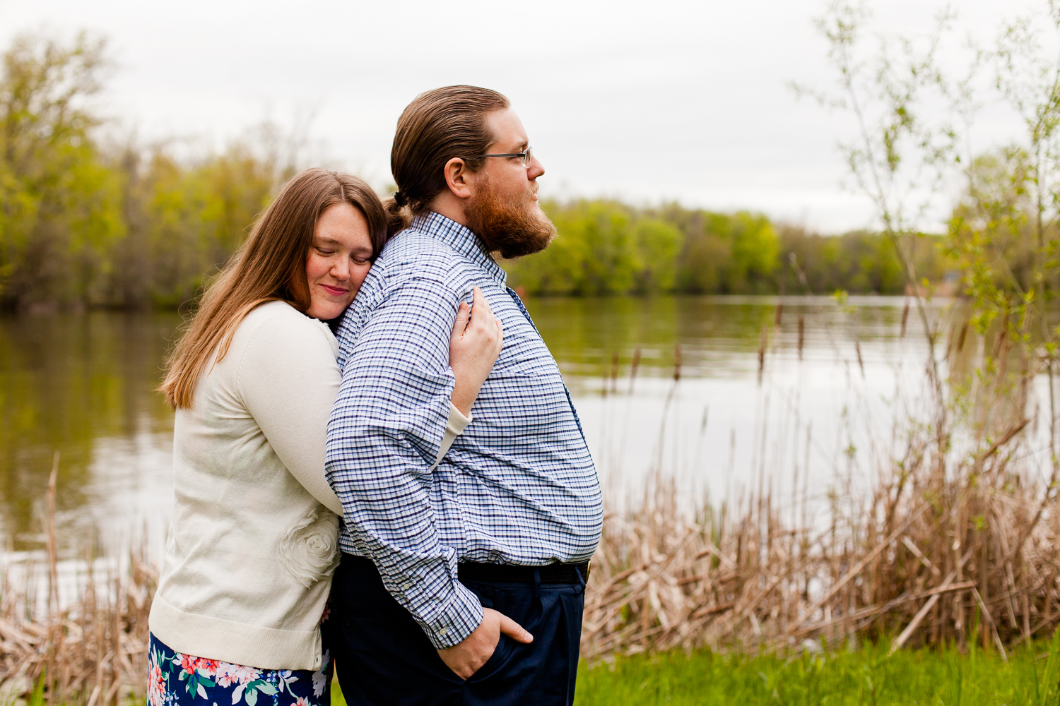 A woman rests against a man at Onondaga Lake Park in Syracuse NY during a spring engagement shoot.