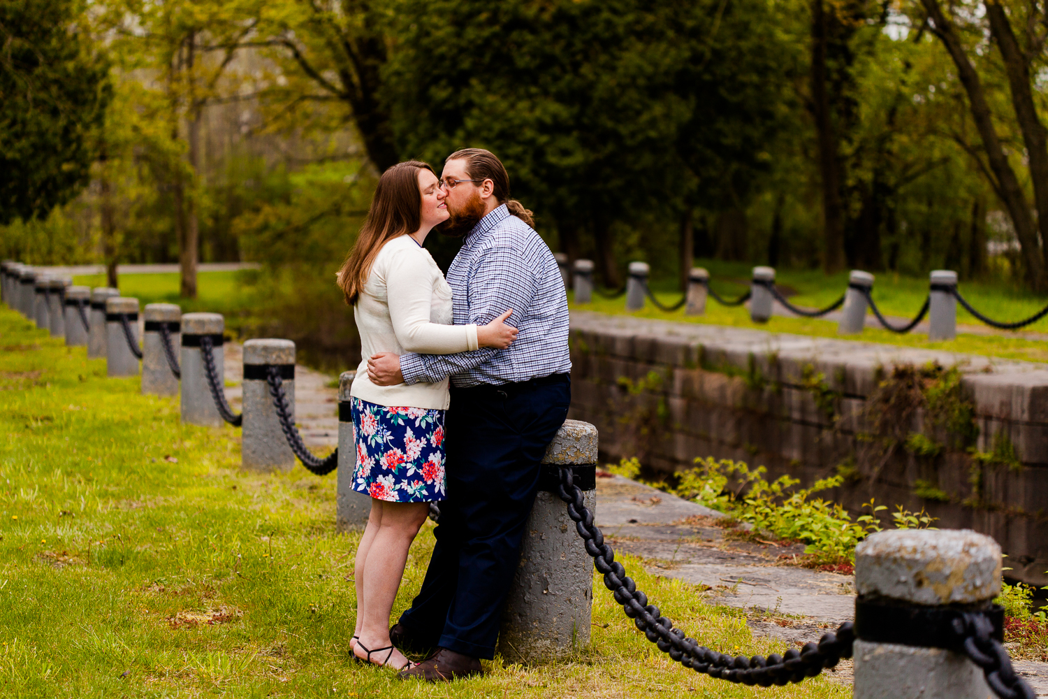 Man and woman leaning up against small fence in Syracuse, NY during a springtime engagement shoot.