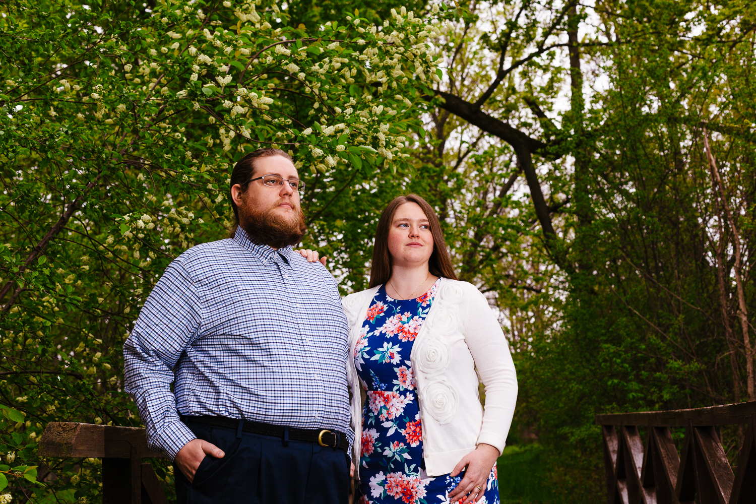 Man with beard in plaid shirt and woman in floral dress with white sweater look off into the distance.