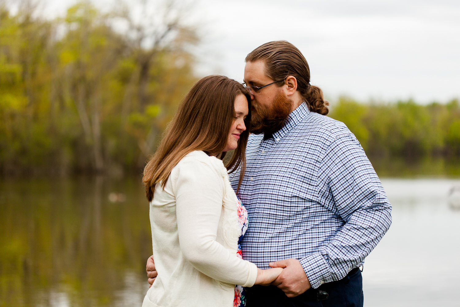 A man kisses the forhead of a woman in a white sweater during their spring engagement session. They are standing in front of a lake.