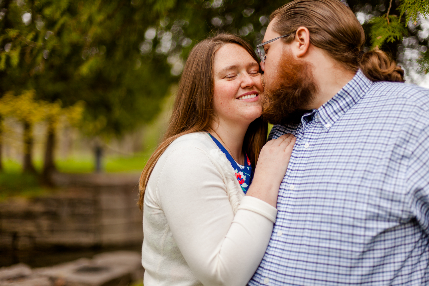 A woman in a white sweater and a floral dress smiles as a man in a blue plaid shirt gives her a kiss. The background is blurry trees. The image is taken by a Syracuse Wedding Photographer.