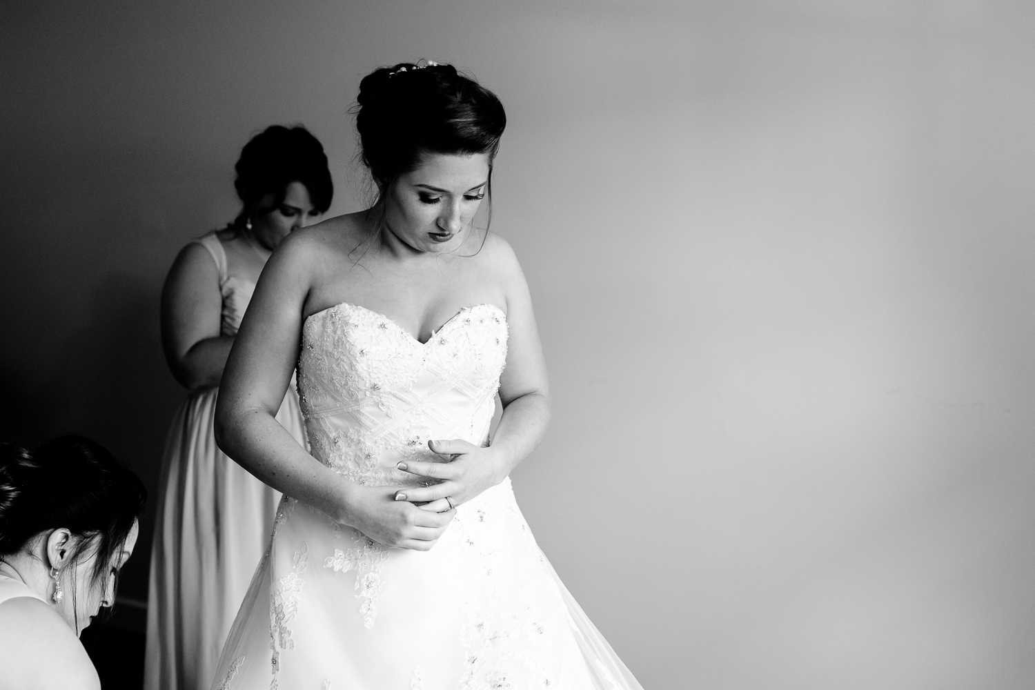 Black and white image of a bride putting on her wedding gown. Her bridesmaids help her.