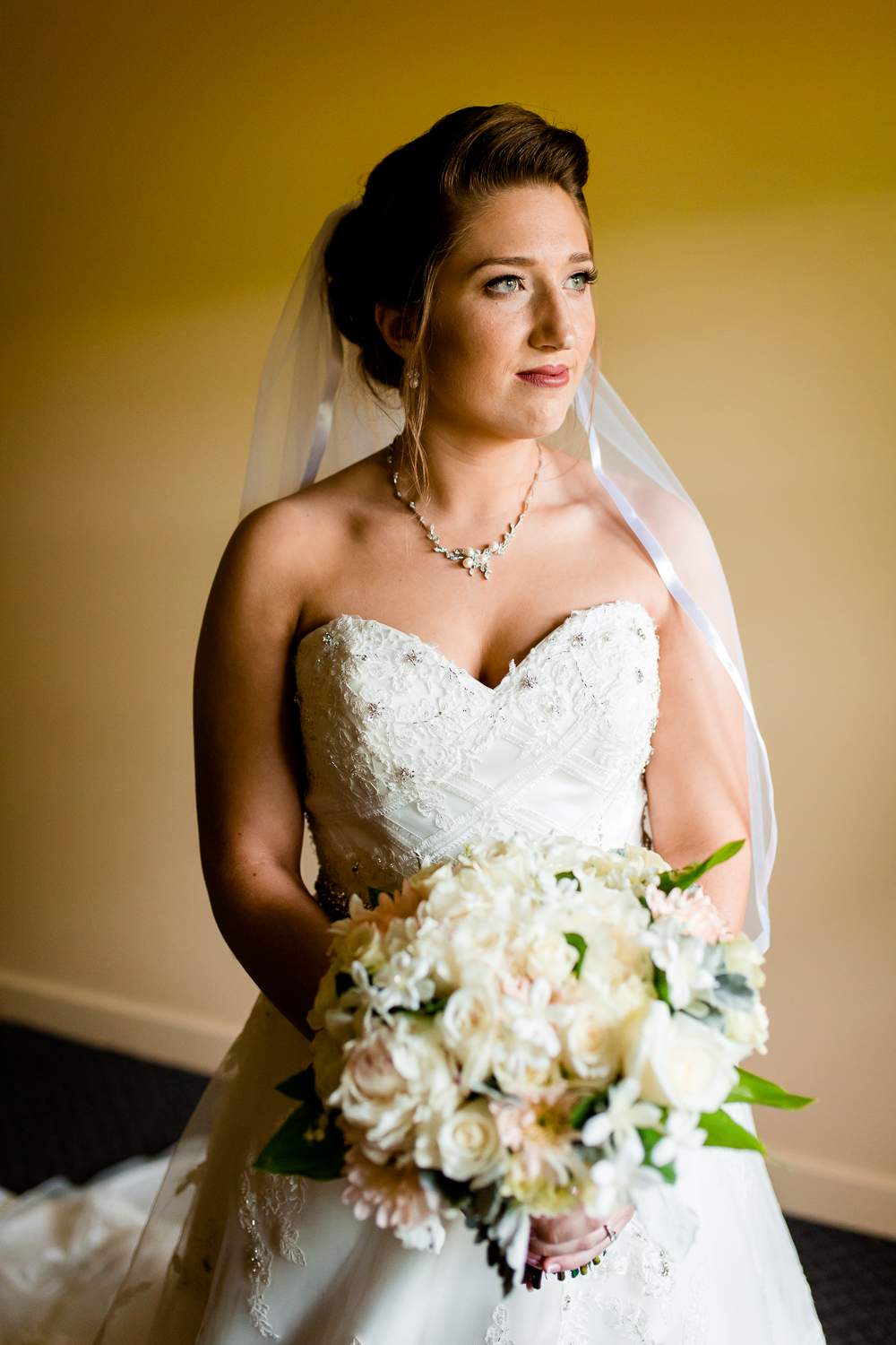 Portrait of bride holding her bouquet of flowers. She is wearing a veil and gazing out of the window.