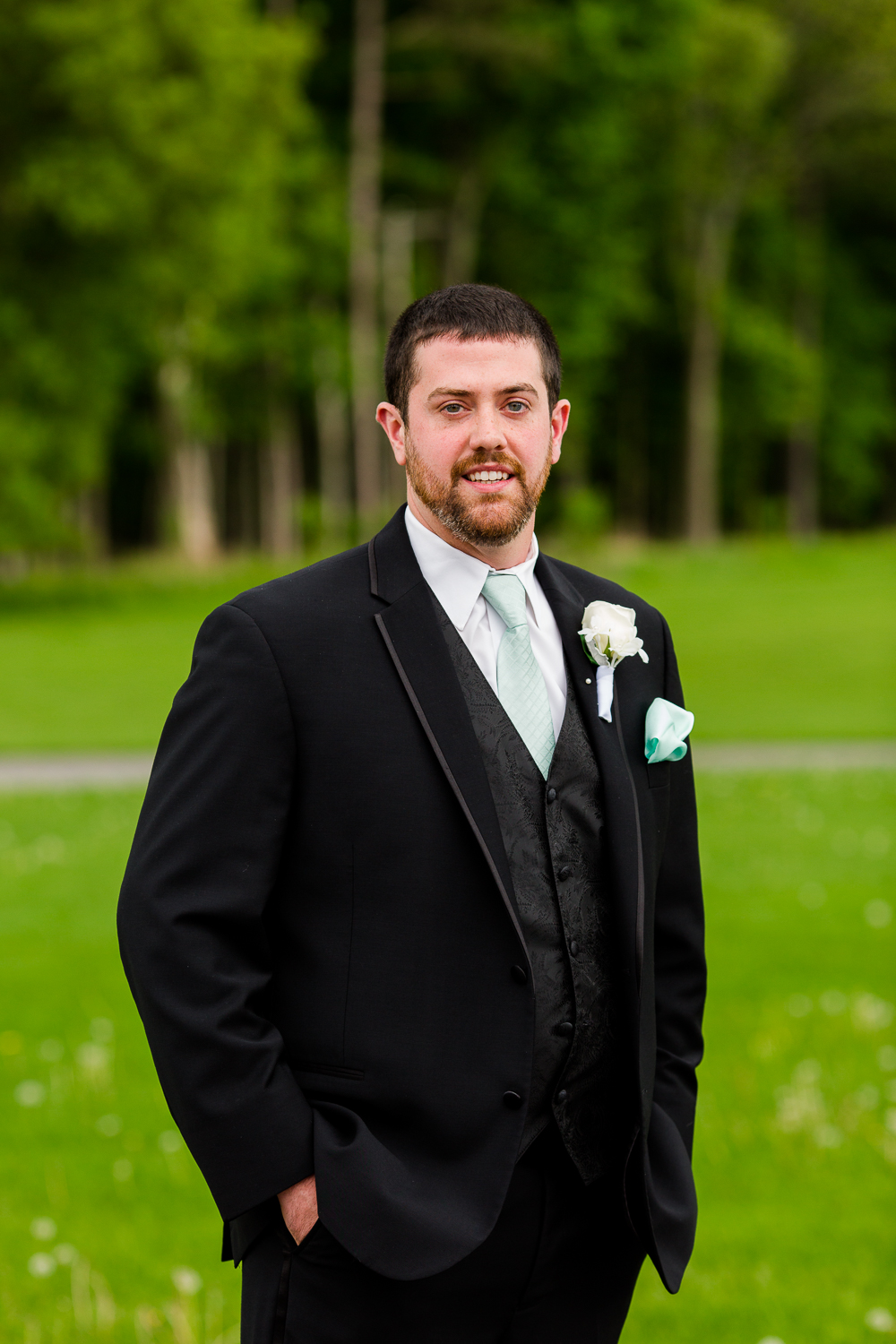 Portrait of a groom in a black tuxedo with a blue tie.