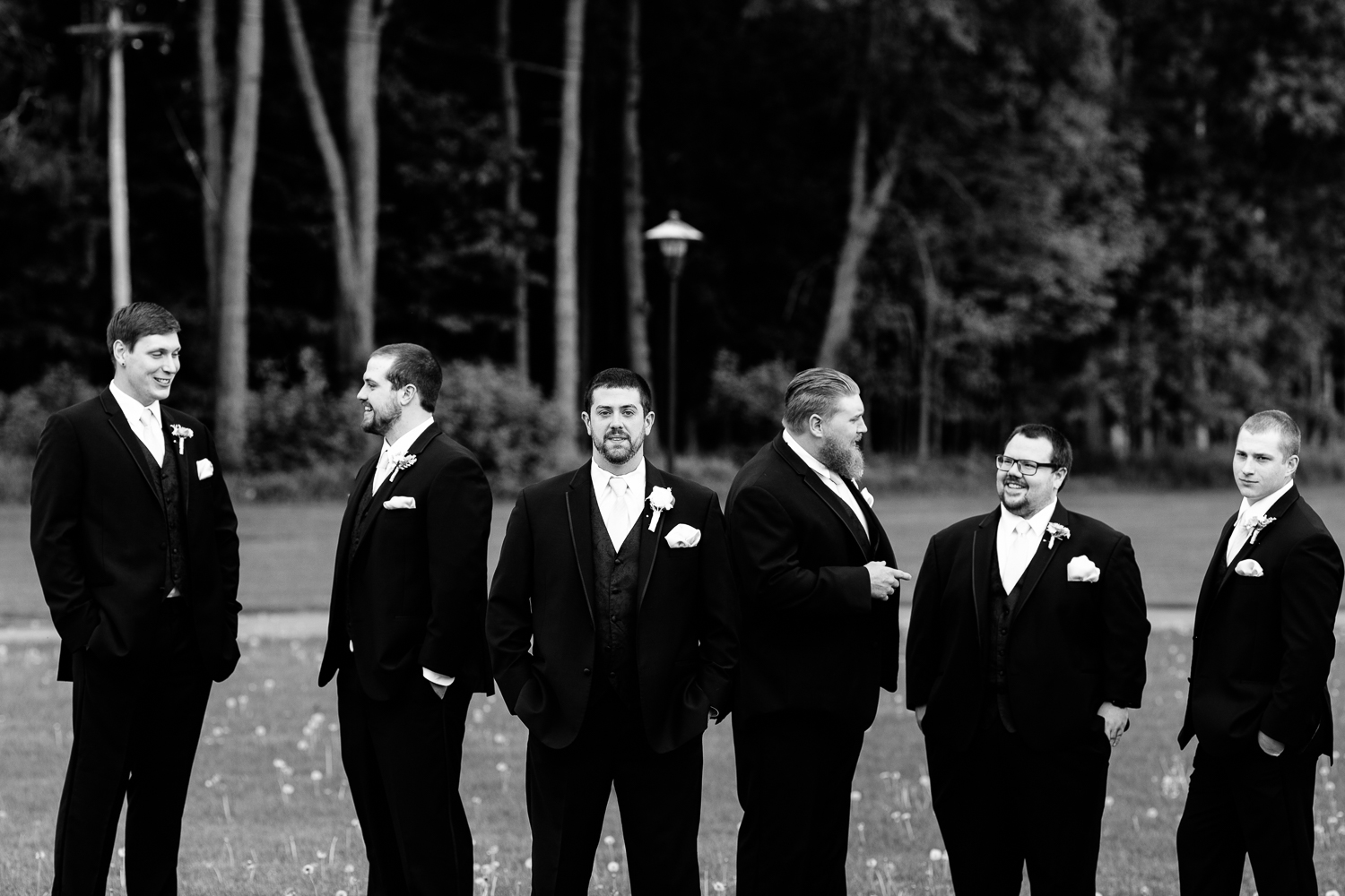 A black and white image of the groom and groomsmen. The groom looks at the camera while the groomsmens talk behind him.