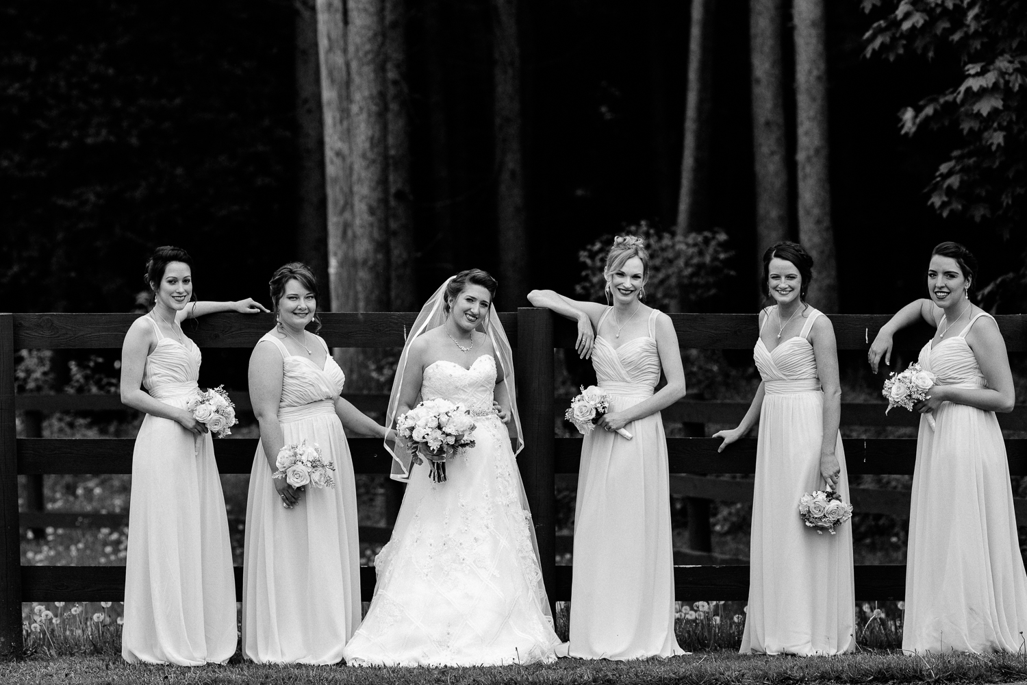 Black and white image of bridesmaids and bride leaning against a fence.
