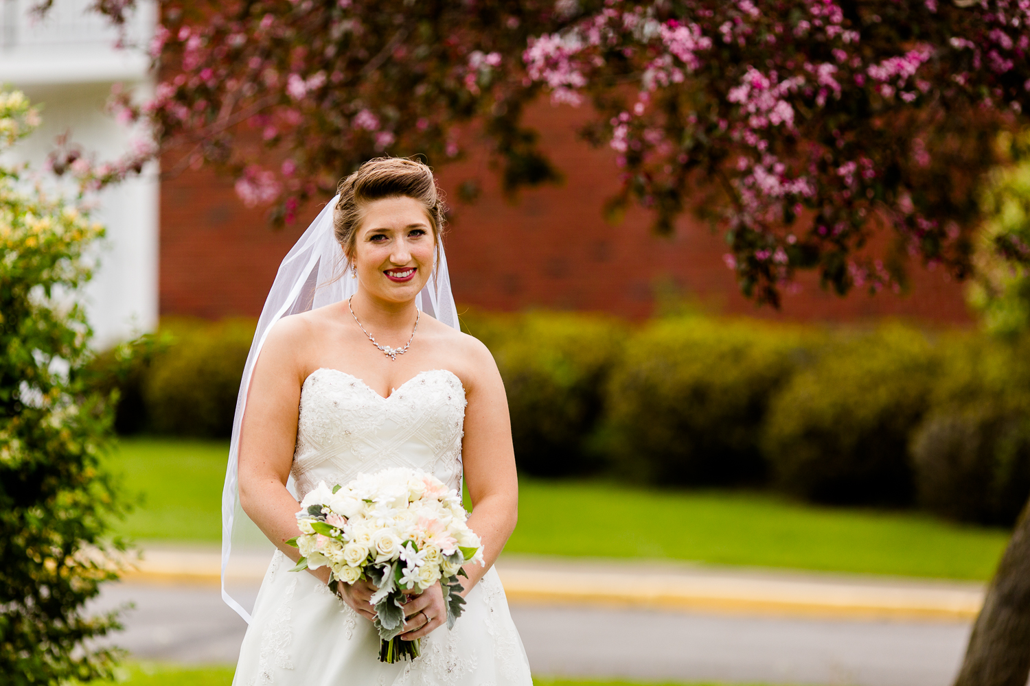Portrait of a bride in front of a flowering cherry tree. She is wearing a white dress and holding a bouquet of flowers.