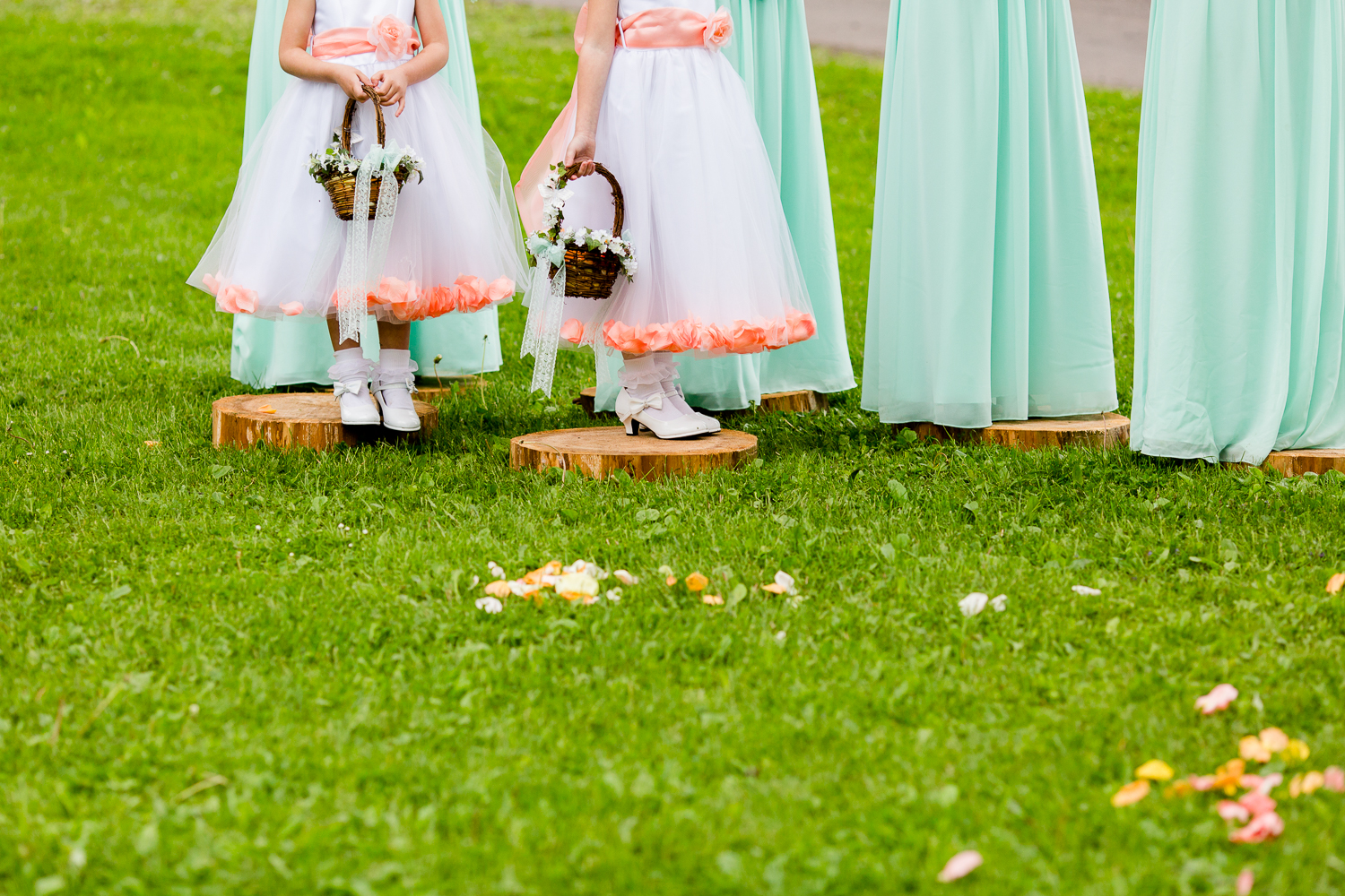 The bottom half of two flower girls. They have rose petals in their dresses and are holding baskets of flower petals.