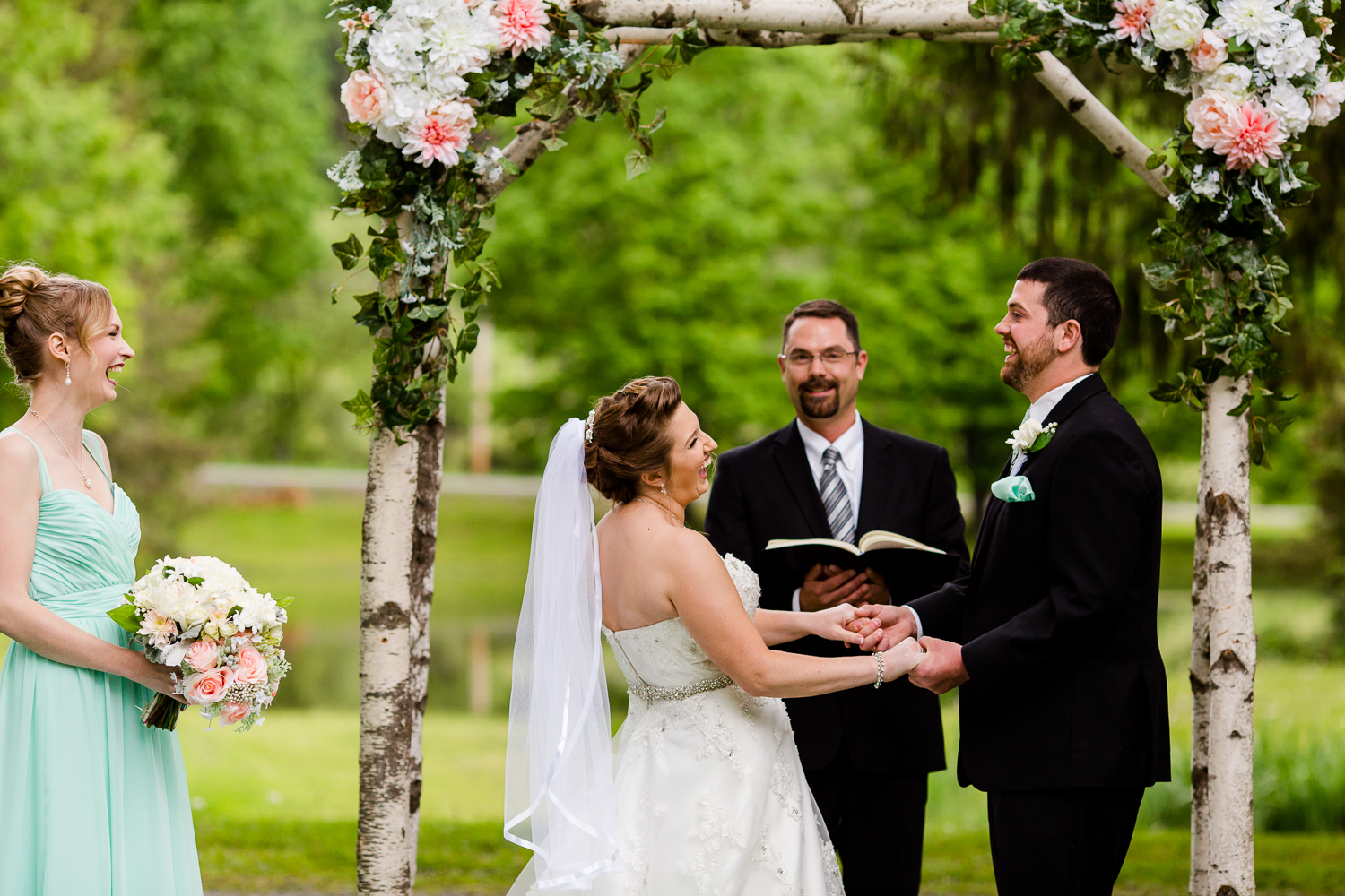 Bride and groom laugh during their wedding ceremony. They are under a birch tree arch. The maid of honor stands next to them laughing.