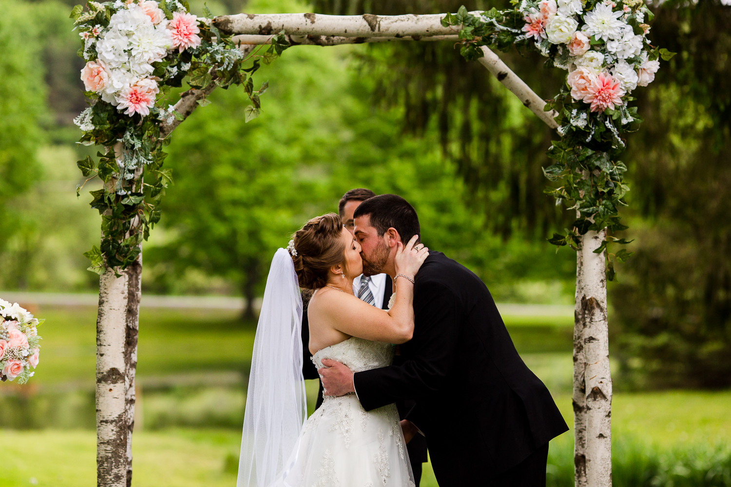 Bride and groom share their first kiss during their outdoor wedding ceremony. They are standing under a birch tree arch adorned with flowers. There is a pond in the background.