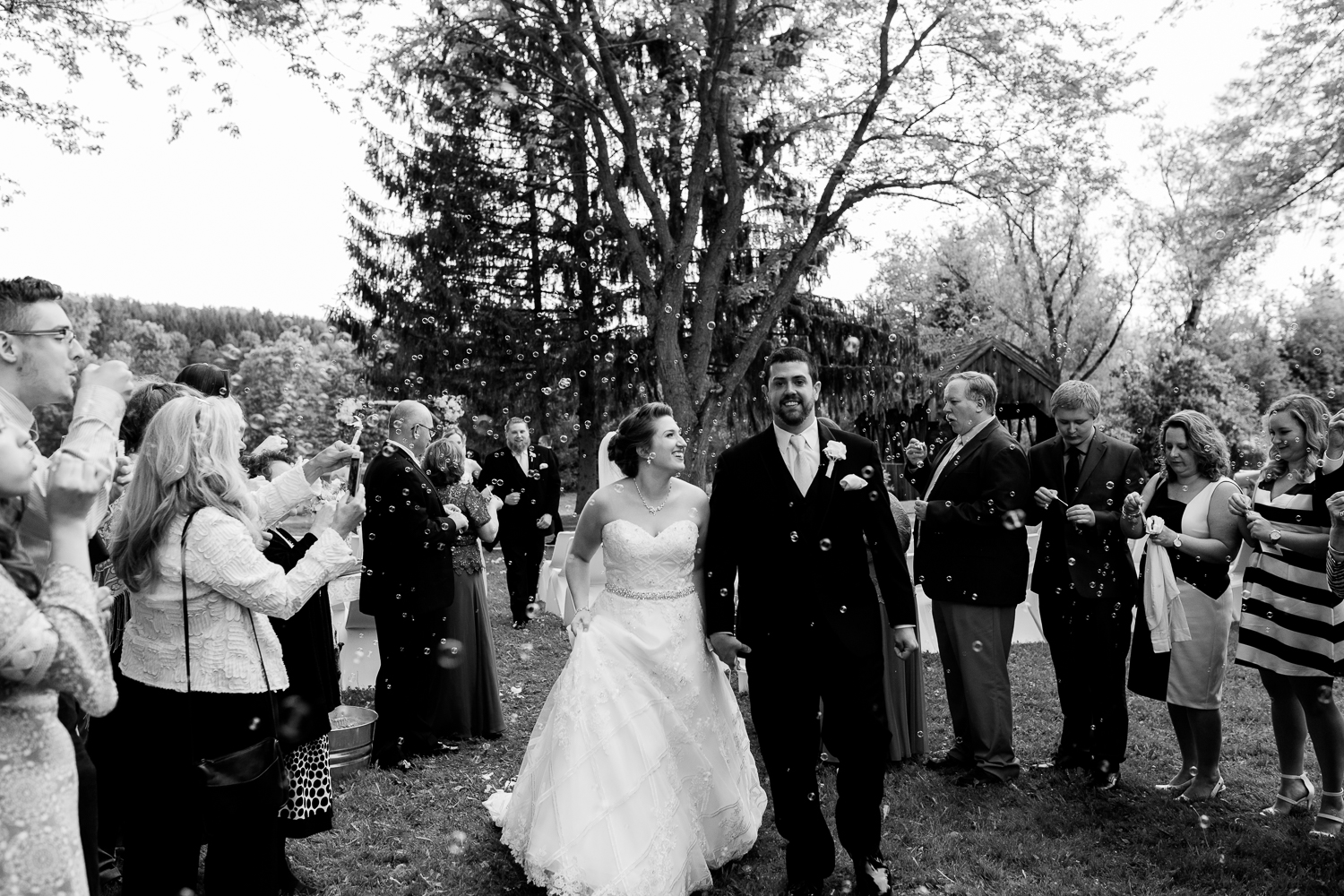Bride and groom walk down the aisle post wedding ceremony as guests blow bubbles around them. The image is in black and white. The bride is smiling up at the groom.