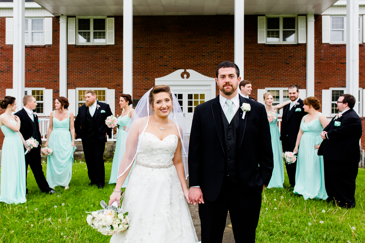 Bride and groom stand in front of the their bridal party. The bridal party mingles in the background while the bride and groom look at the camera. They are in front of a red brick building with a white awning.