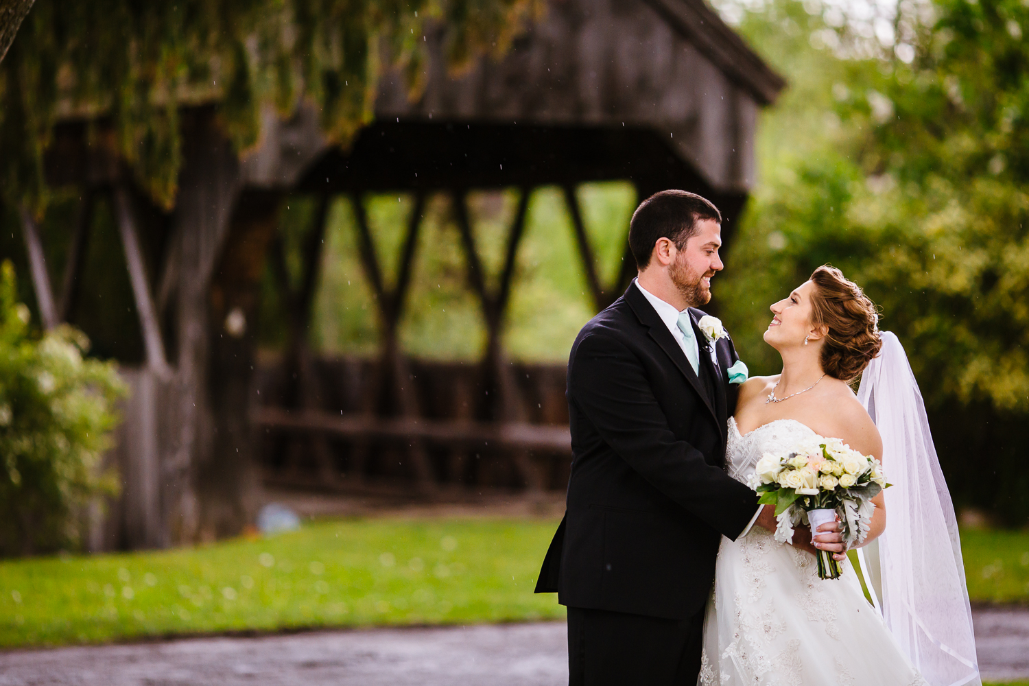 Bride and groom look at each other. They are standing in front of a covered wooden bridge.