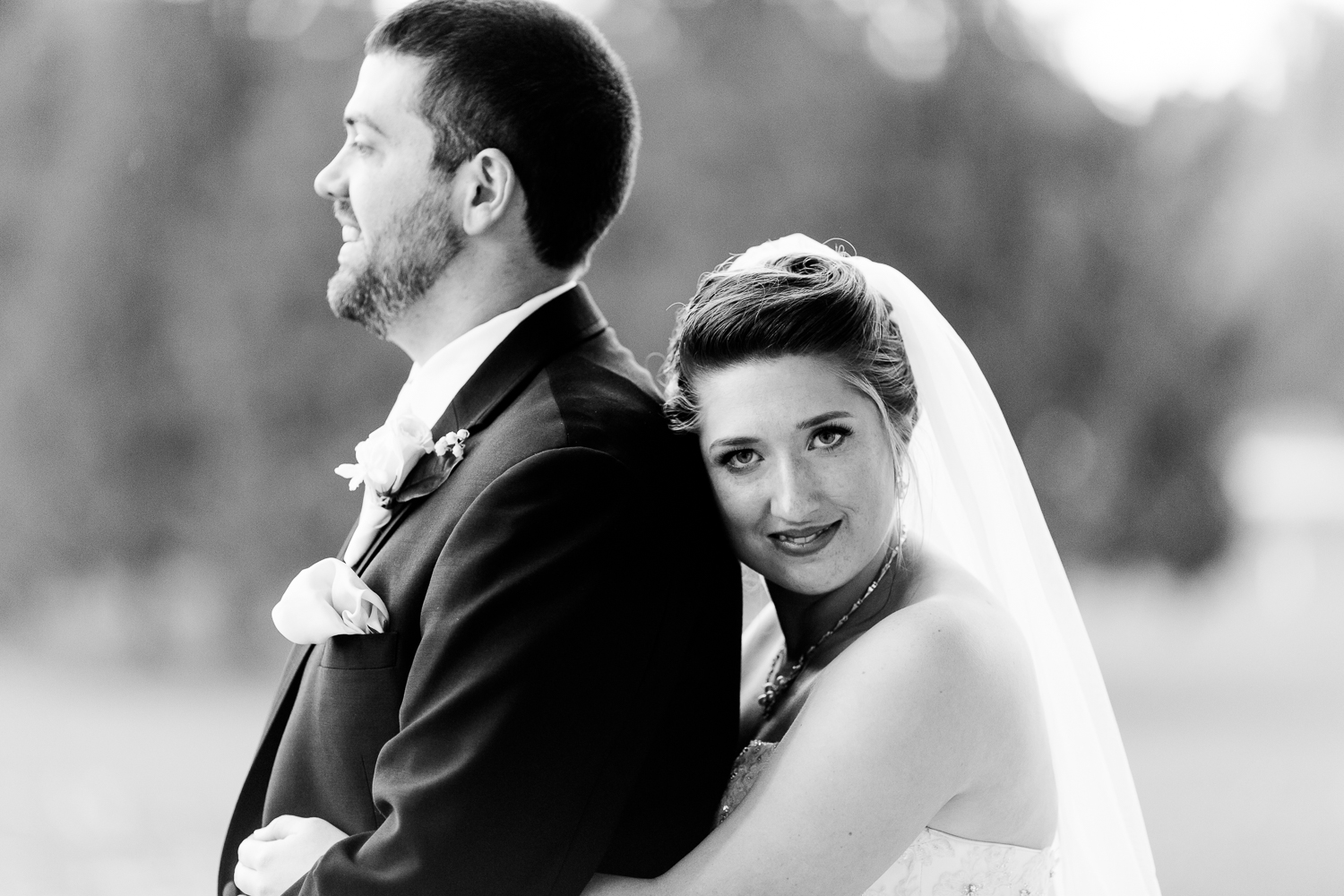 Black and white image of the bride and groom. The bride rests her head on the back of the grooms shoulder. She gazes into the camera while the groom looks off into the distance.