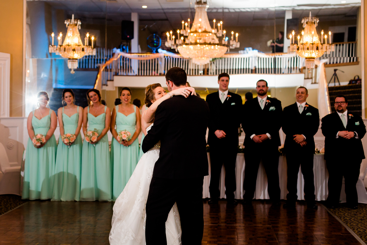 First dance of bride and groom. The wedding party looks on. There are chandeliers hanging above them.