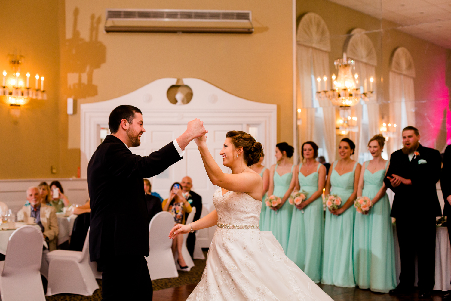 Groom spins bride during first dance at their wedding reception.
