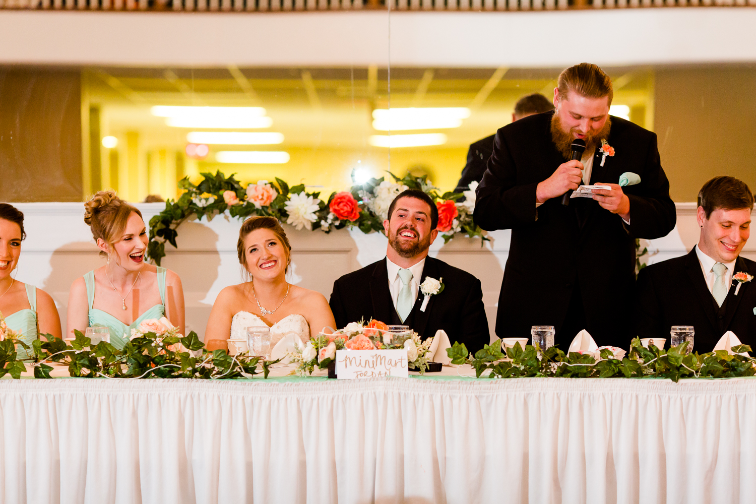 Best man gives a toast to the bride and the groom. The couple smiles.