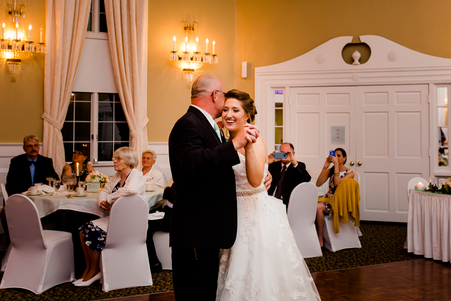 The bride and her father share a sweet moment during the father daughter dance at her wedding. The father kisses the side of her head while the bride smiles.