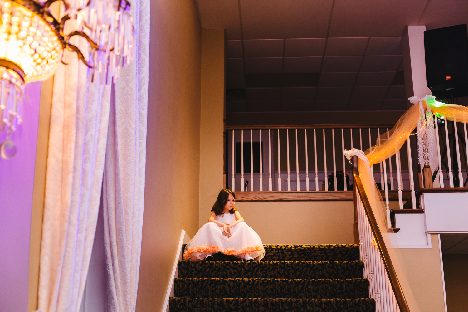 Flower girl sits on the stairs at the wedding reception. She is looking down on the dance floor.