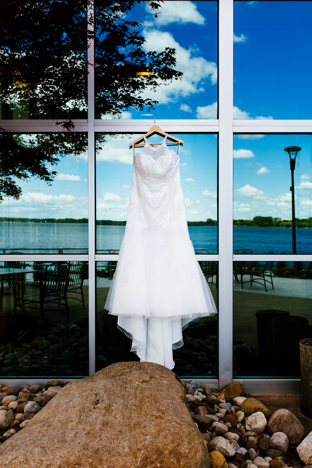 White wedding gown hanging on reflective windows.